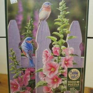 Bluebirds sitting on picket fence with pink hollyhocks