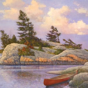 Red Canoe tucked behind a rock with a rock island and windswept pine trees behind